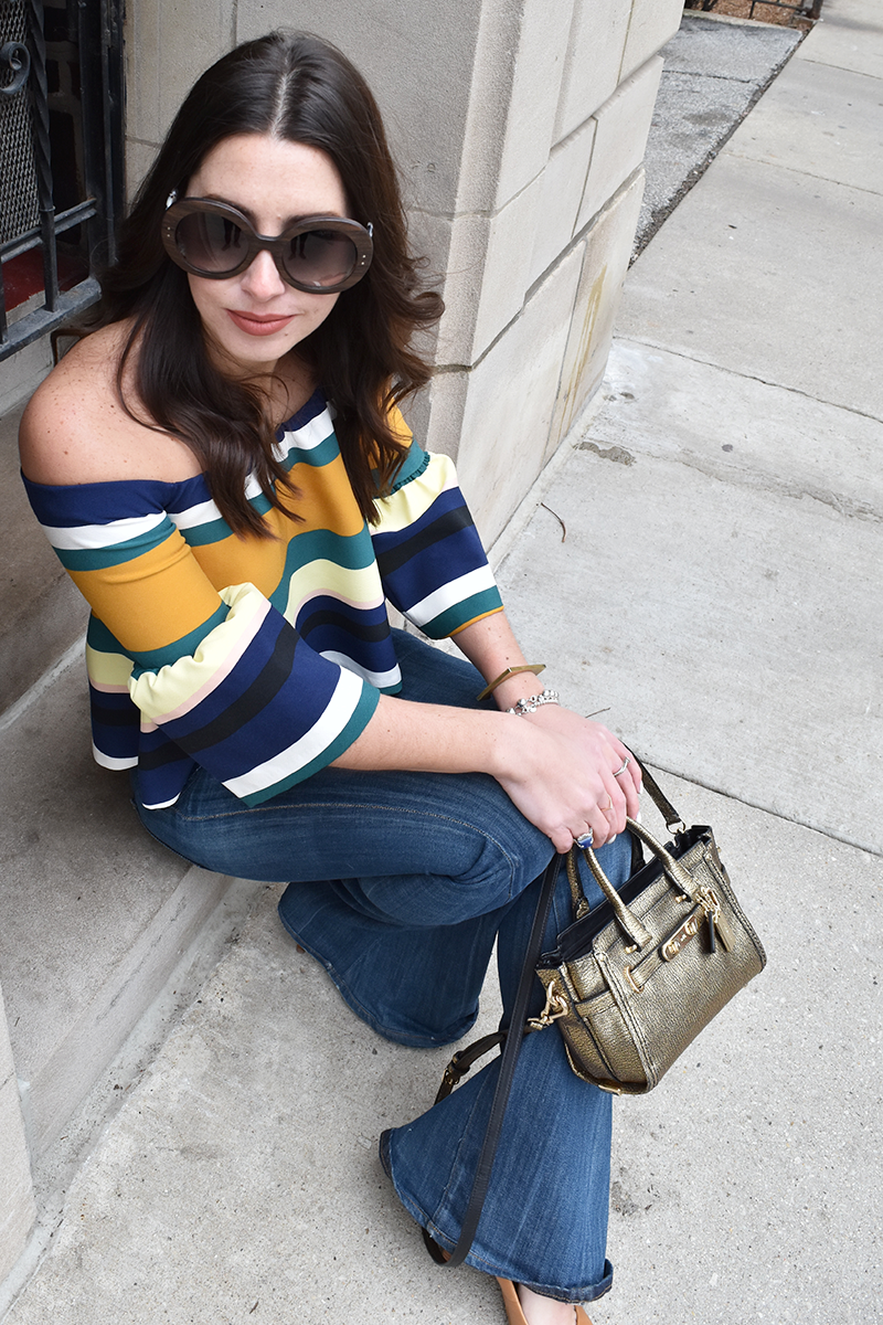 Throwin' It Back to the 70's | Zara striped off-the-shoulder top, Citizens of Humanity flared jeans, Nine West pointed toe heels, Coach Swagger 20 bag in metallic pebble leather, Prada PR 27ns sunglasses