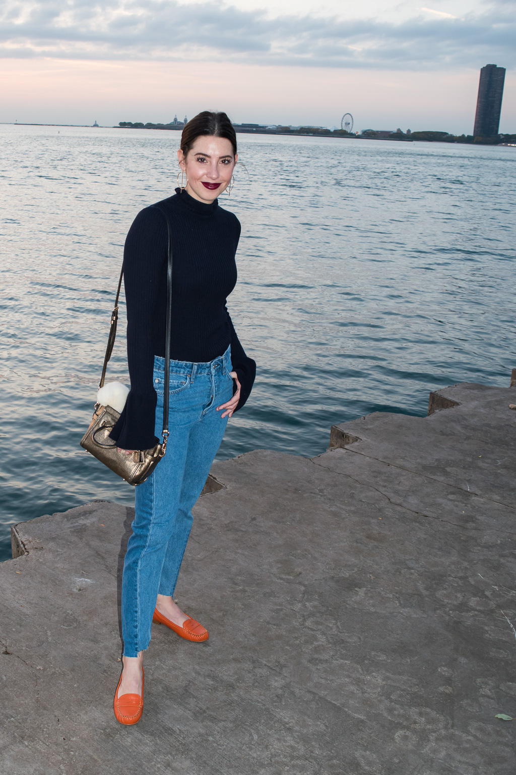 It's all in the details when putting an outfit together. Keeping your outfit simple is great, but create visual interest through small details that pop like bell-sleeves, scallops, jeans with high-low cut hems, large hoop earrings, and colorful orange loafers.